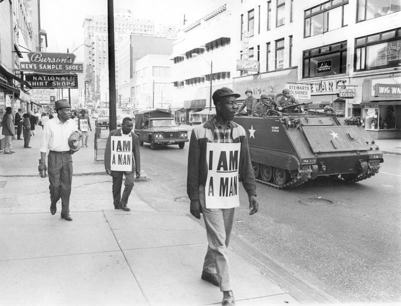 Memphis sanitation strikers marching down Main Street while National Guardsmen in an armored personnel carrier patrol alongside, March 1968&lt;br /&gt;<br />