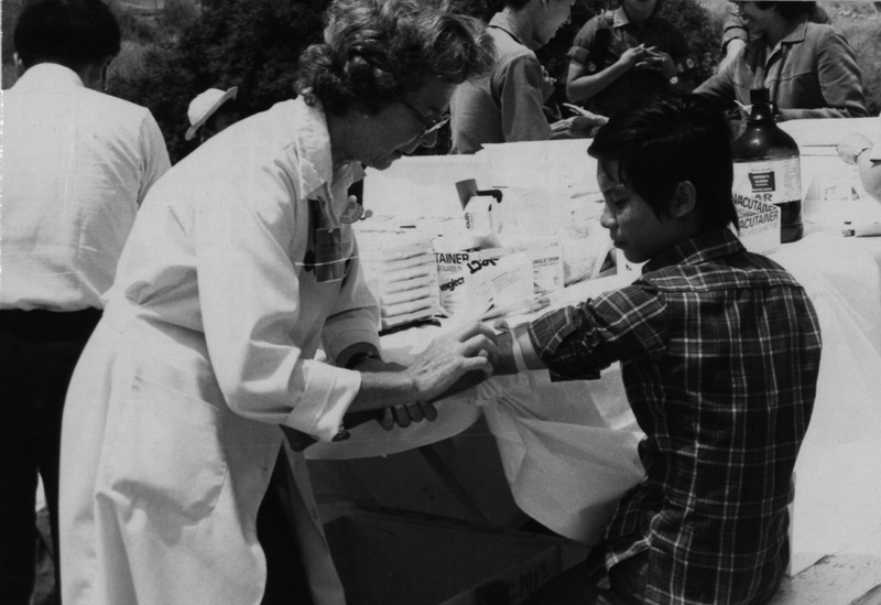 Camp Pendleton, California.  Mrs. Joyce Davenport, a Red Cross Volunteer from La Jolla, CA prepares a Vietnamese Refugee for an immunization shot, May 17, 1975