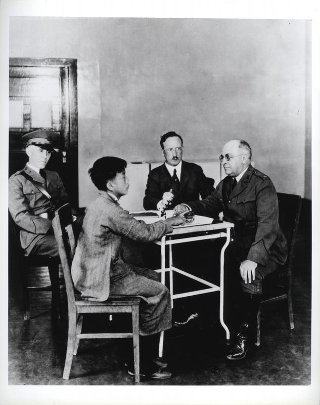 U.S. Public Health Service (PHS) and Immigration Service officers interrogating a Chinese immigrant at a meeting of the Board of Special Medical Inquiry, Angel Island, California, 1923, photograph by P.E. Brooks