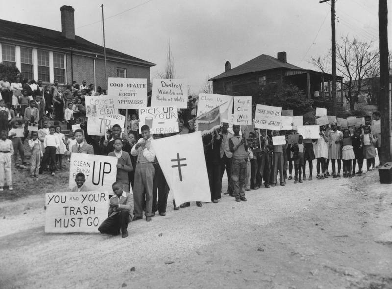 African American students holding posters advocating trash pick-up and clean neighborhoods to prevent the spread of disease in Atlanta, Atlanta Anti-Tuberculosis Association campaign, 1945