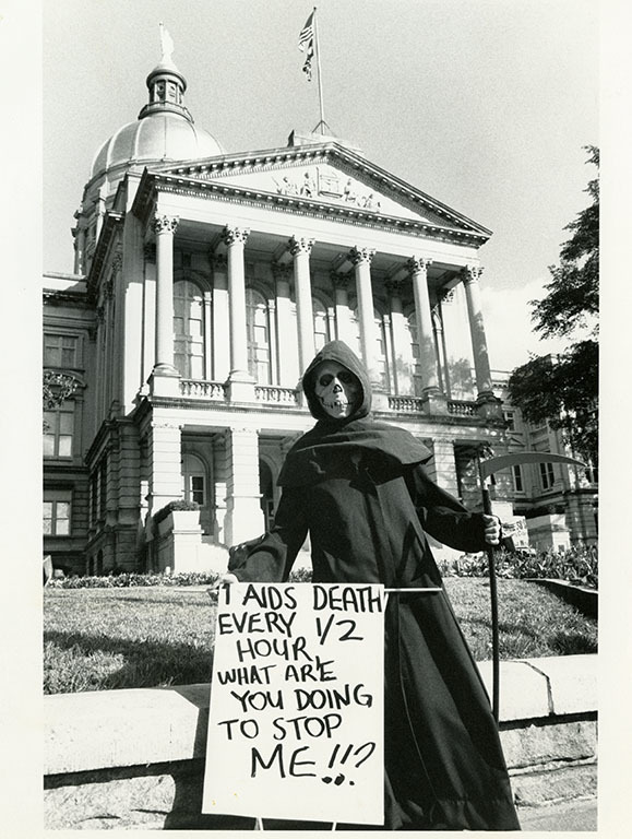 "Photograph -- Grim Reaper holds sign saying ""1 AIDS Death Every 1/2 Hour, What Are You Doing to Stop Me!!?"" in front of the Georgia State Capital."