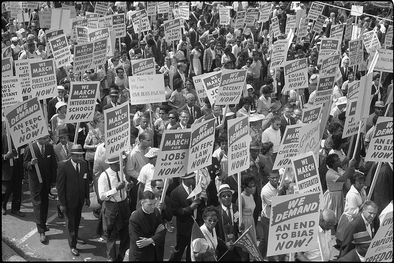 Demonstrators marching in the street holding signs during the March on Washington, 1963