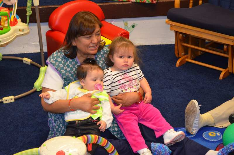 Tewa teacher Judy holding Lilyana and Eliana in the Early Childhood Center, Pueblo of Pojoaque, New Mexico, February 2013