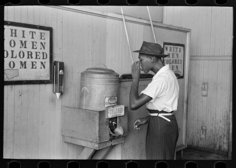 "Negro drinking at ""colored"" water cooler in streetcar terminal, Oklahoma City, Oklahoma, July, 1939"