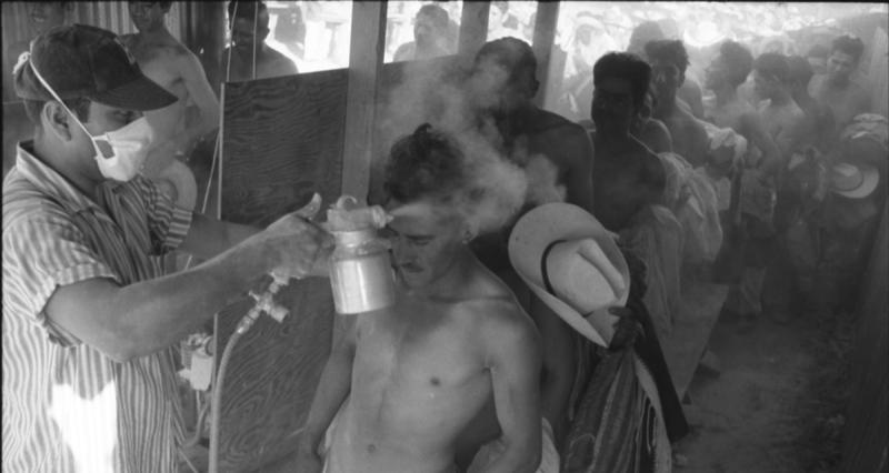 Upon crossing the bridge from Mexico, men were led through a makeshift booth, and sprayed with DDT by Department of Agriculture personnel.  Photograph by Leonard Nadel, 1956