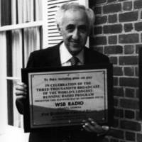 Elmo Ellis with three thousandth broadcast plaque