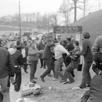 """AFSCME Local 1644-led sanitation strike, Atlanta, Georgia, March 1970. These photographs are taken outside the City of Atlanta Construction Department office and warehouse (110-111 Hill Street). Protesters are apparently attempting to block strikebreakers from crossing the picket-line and entering the office area. The photograph series is labeled """"Garbage Strike."""""""