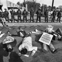 Photograph -- Police stand in front of the Centers for Disease Control as gay activists from ACT UP stage a 'die-in' to protest the CDC's handling of the AIDS crisis, Atlanta, Georgia, January 9, 1990.