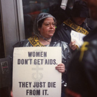 "Photograph -- woman holding sign that reads ""Women Don't Get AIDS They Just Die From It"""