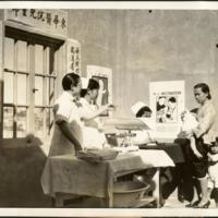 Dr. Rose Goong Wong (far left) coaxing a child at the Well Baby Clinic, Chinatown, San Francisco, 1934