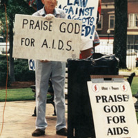 """Photograph -- Counter protester with sign saying """"Praise God for AIDS"""""""