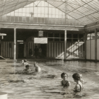 FDR receiving physical therapy or exercising with assistance in an indoor pool at Warm Springs, GA, 1928.