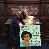 Linda Wilder Bryan and Lisa Flaherty with her protest sign