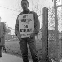 """AFSCME Local 1644-led sanitation strike, Atlanta, Georgia, March 1970. These photographs are taken outside the City of Atlanta Construction Department office and warehouse (110-111 Hill Street). Protestors are apparently attempting to block strikebreakers from crossing the picket-line and entering the office area. The photograph series is labeled """"Garbage Strike."""""""