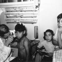 A doctor examines a boy's ears onboard the M/S Hygiene, 1956
